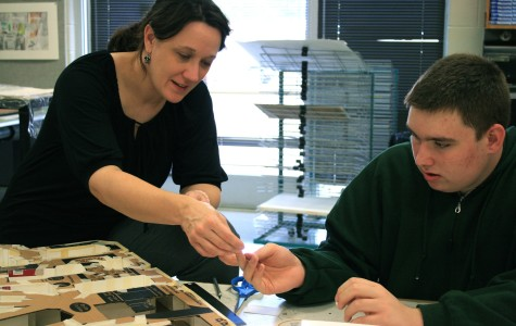 Mrs. Victoria Cunningham works with Shane Fenton during an art class.