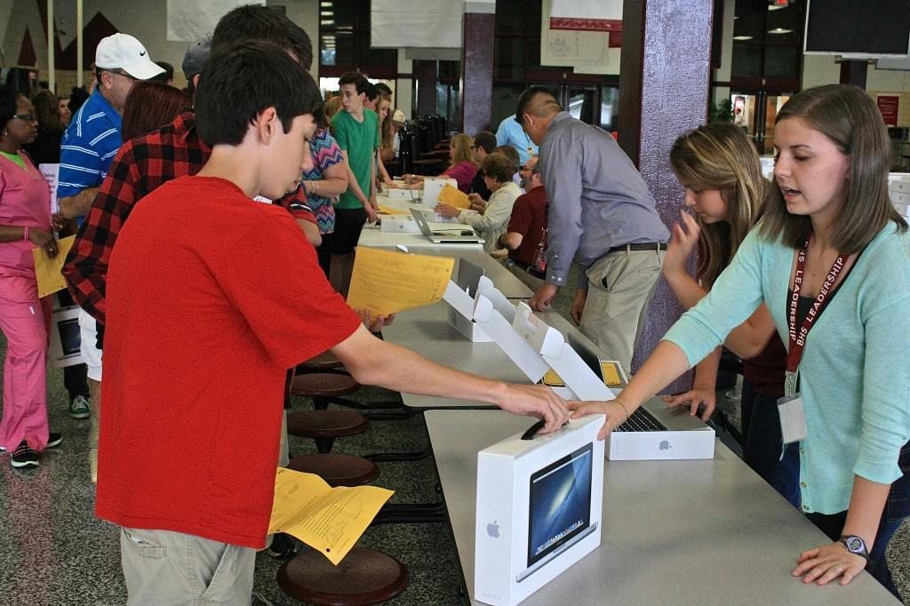 Students and parents line up in the cafeteria to pick up the new MacBook Pros. The rollout ends on Thursday night.