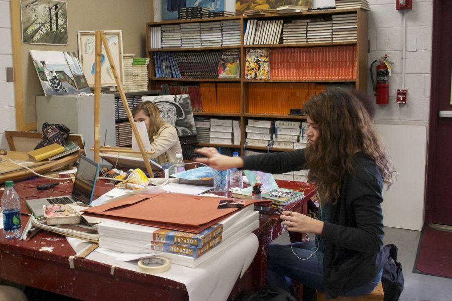 Seniors+Corinne+Brown+and+Maggie+Berry+finish+last+minute+preparations+for+the+%22Uncommon+Core%22+art+show.
