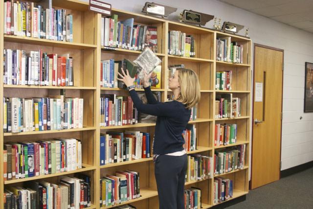 Ms.+Kristen+Heffern+restocks+the+shelves+in+her+new+position+in+the+Bearden+library.