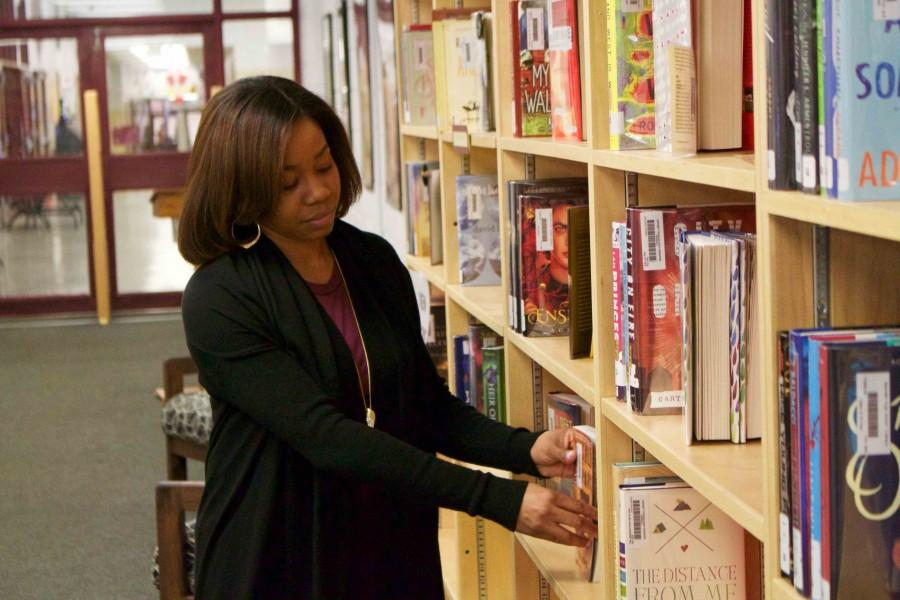 Ms.+Erika+Long+puts+one+of+her+favorite+books+on+display+in+the+BHS+library.