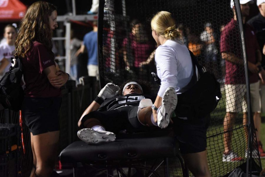 Bearden trainer Kristen Cook (right) works with junior receiver Hayden Candela while senior Lauren Stuckey looks on. Stuckey has been a part of Bearden's sports medicine program this year.