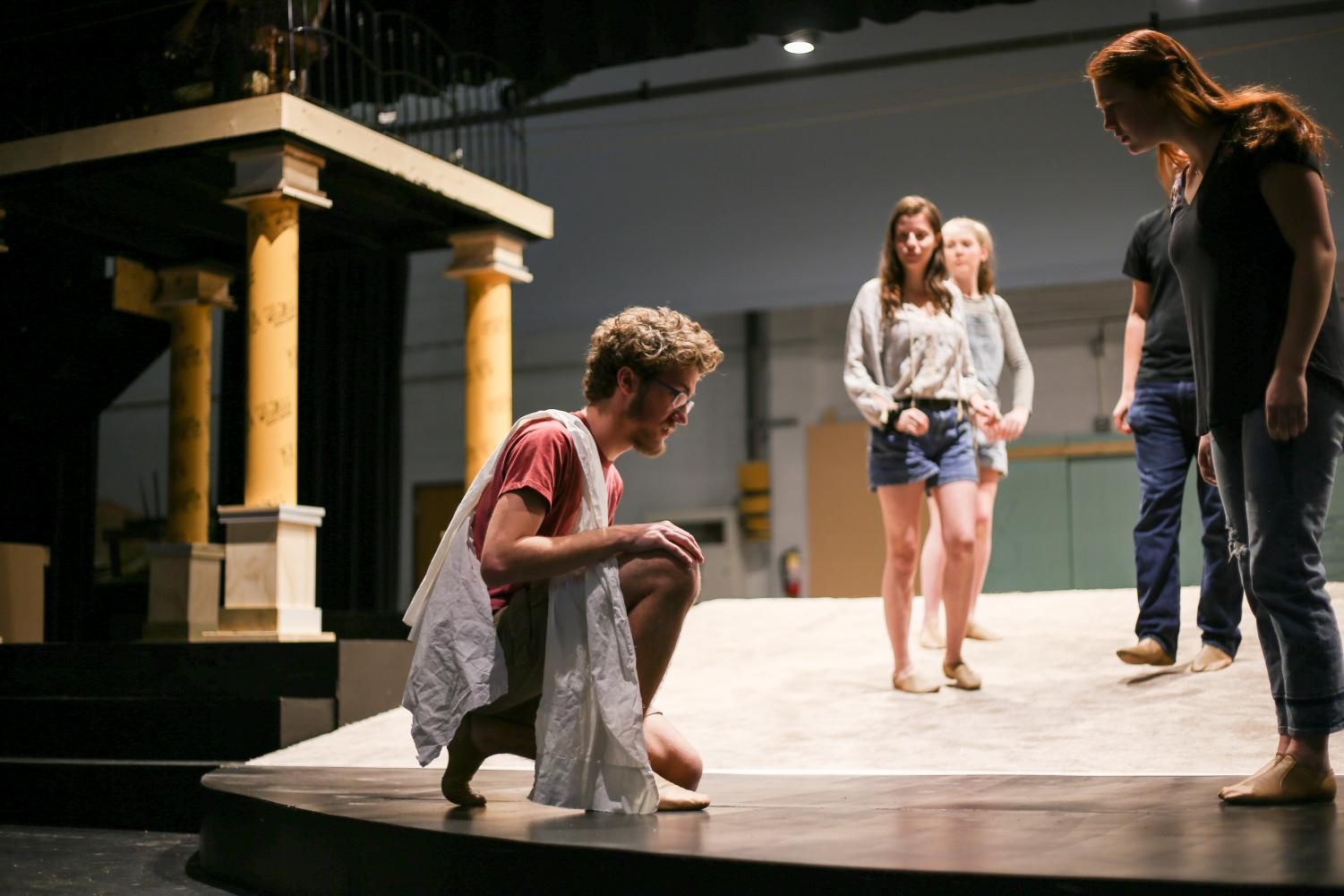 Seth Reynolds (Odysseus) kneels before Becca Siegel (queen of Phaeacia) during rehearsal for Bearden's production of The Odyssey.