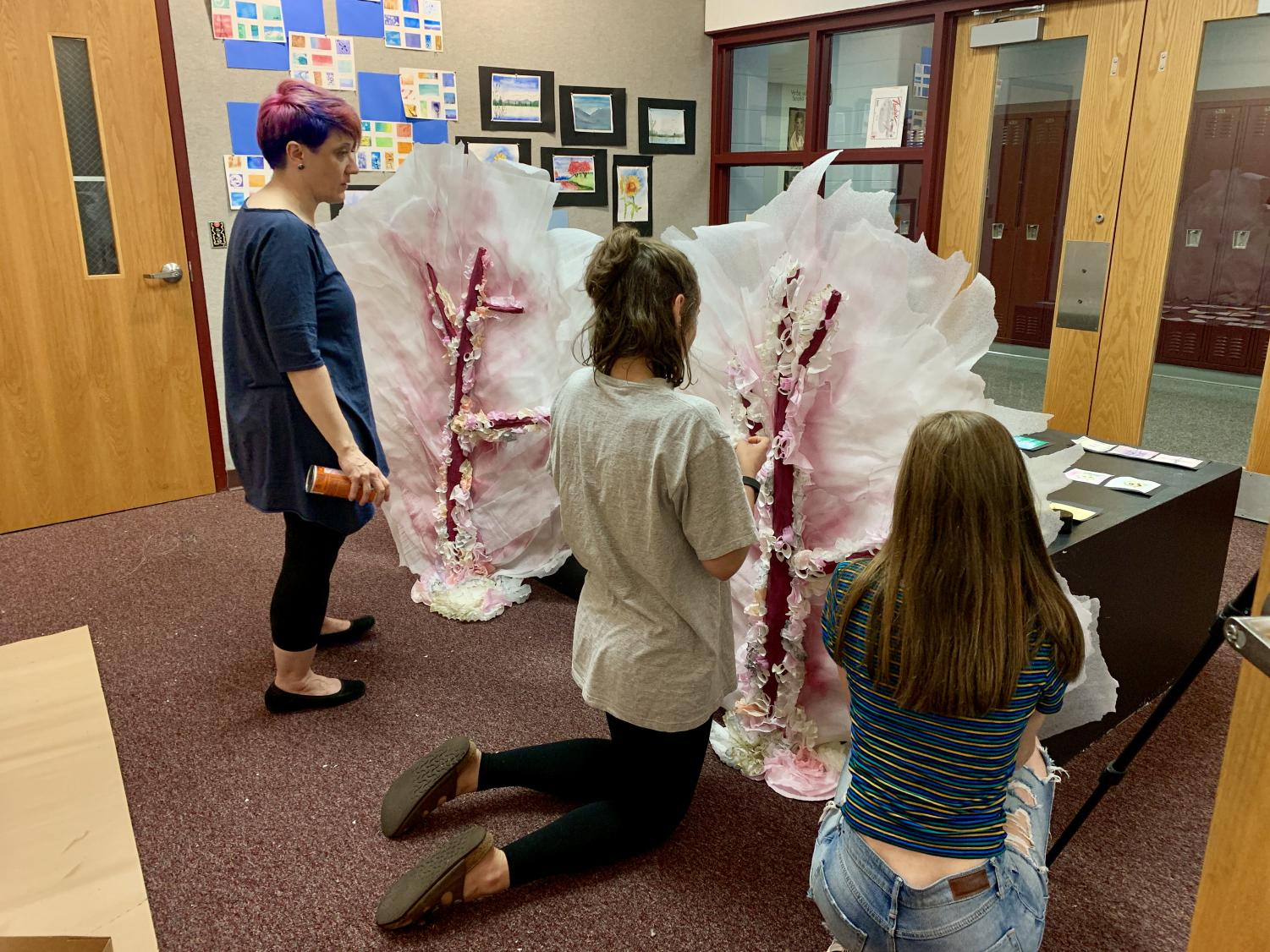 Mrs. Victoria May looks on as prom committee members work on designing decorations in the art gallery this week.