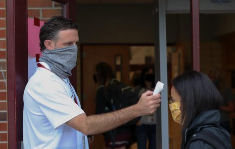 Mr. Donald Balcom takes a student's temperature before school.