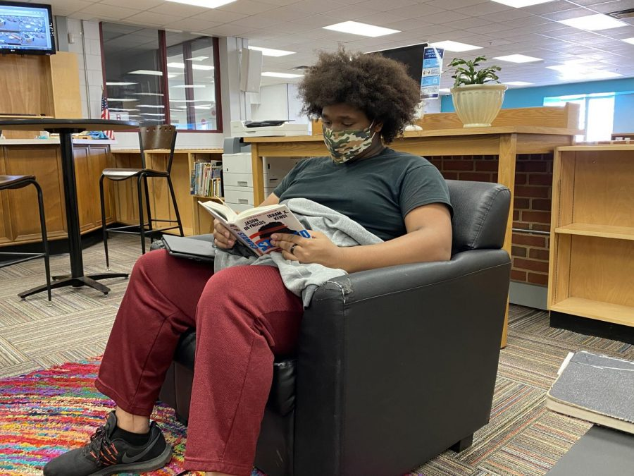 Senior Dante Brown reads one of the library's new selections.