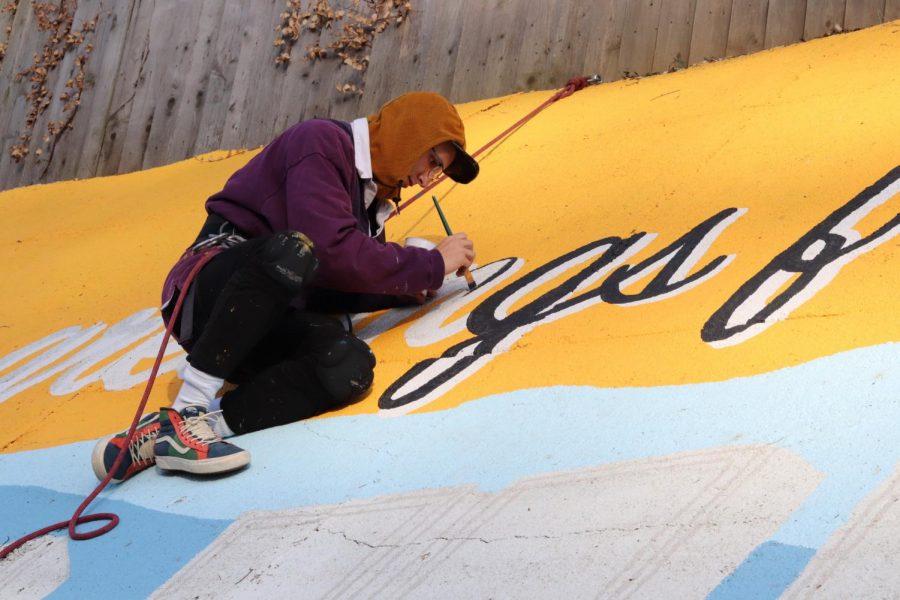 Bearden alum Cooper Moldrup paints a mural on a retaining wall across from Blue Grass Elementary.