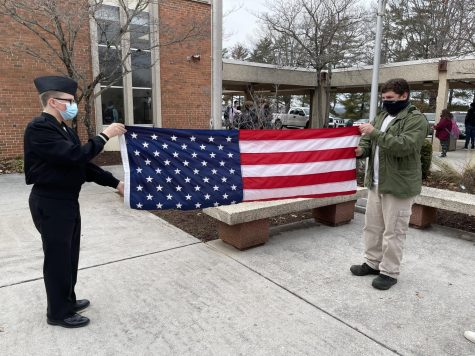 Freshmen Aaron Sturgill (left) and Benjamin Thacker (right) fold the American flag after school last week.